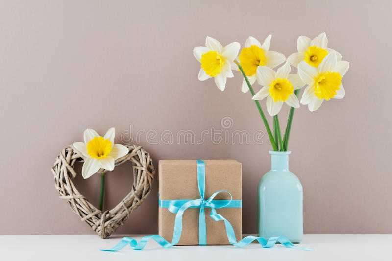 Narcissus or daffodil flowers in vase, wicker heart and gift box for greeting on mother day. royalty free stock photo