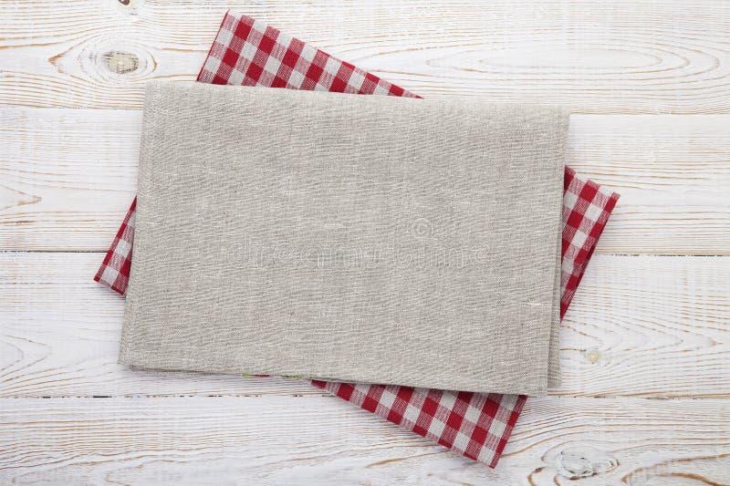 narcotize Pila di asciugamani di piatto variopinti su derisione di legno bianca di vista superiore del fondo della tavola su fotografia stock