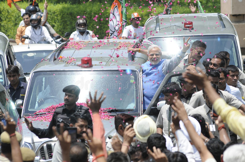 Narendra Modi in Delhi. NEW DELHI-MAY 17: Indian Prime Minister Narendra Modi being surrounded by media and his security guards while he is hanging onto his car royalty free stock images