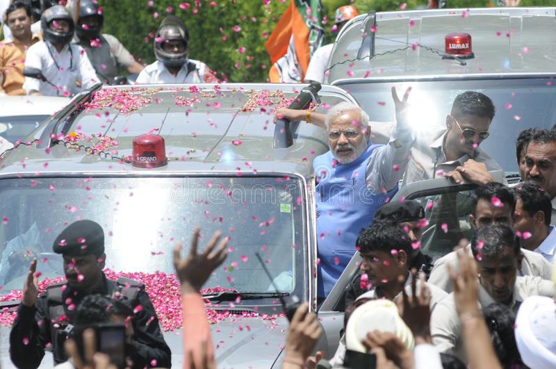 Narendra Modi in Delhi. NEW DELHI-MAY 17: Indian Prime Minister Narendra Modi showing victory sign while hanging onto his car after wining the Indian National stock images