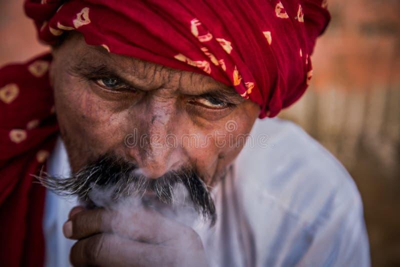 Narghilé di fumo dell'uomo che porta turbante rosso fotografia stock libera da diritti