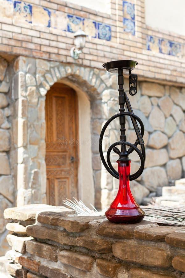 Narghilé nero con la lampadina vermiglia in caffè antico orientale autentico, all'aperto Vista frontale, integrale verticale immagine stock libera da diritti