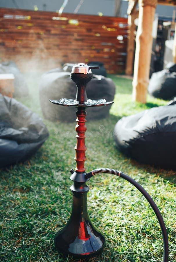 Nargile czerń na ulicie Nargile na trawie Tło stylu życia pojęcie Tło czarni pouffes zdjęcia stock