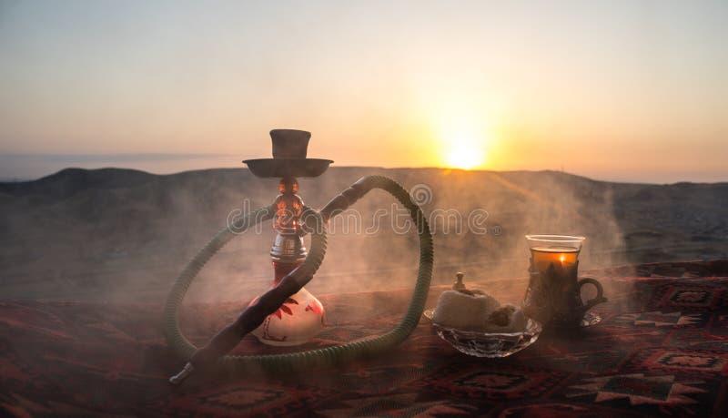 Nargile gorący węgle na shisha pucharze robi chmurom kontrpara przy pustynny plenerowym Orientalny ornament na dywanowej wschodni fotografia royalty free
