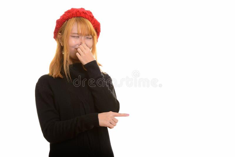 Nariz asiático bonito novo da coberta da mulher que aponta o dedo no lado fotografia de stock royalty free