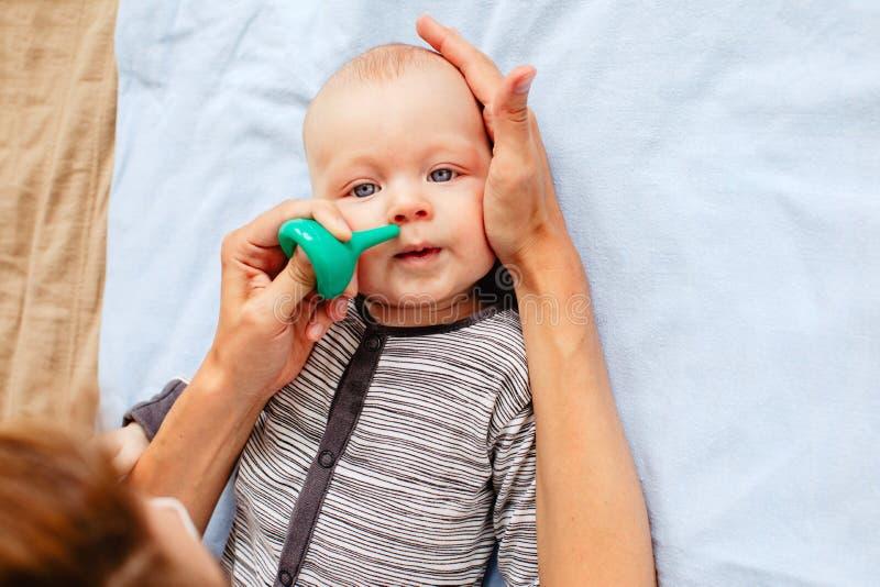 Nariz de limpeza da mãe do bebê bonito imagens de stock
