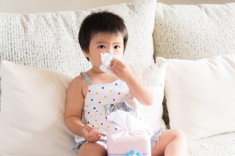 Nariz de limpeza ou de limpeza da menina asiática pequena doente com tissu imagem de stock