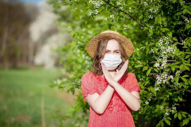 Nariz que sopla de la chica joven y estornudo en tejido delante del ?rbol floreciente Alerg?nicos estacionales que afectan a gent fotos de archivo