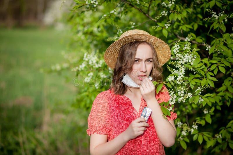 Nariz que sopla de la chica joven y estornudo en tejido delante del ?rbol floreciente Alerg?nicos estacionales que afectan a gent imagen de archivo libre de regalías