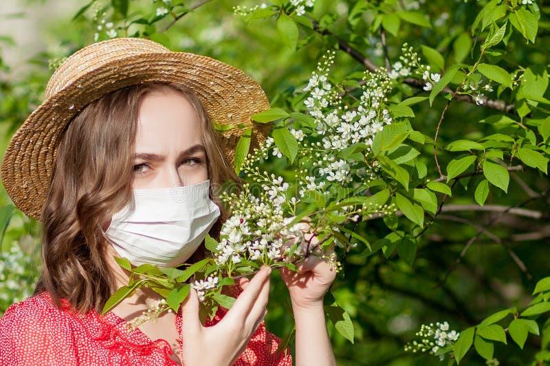 Nariz que sopla de la chica joven y estornudo en tejido delante del ?rbol floreciente Alerg?nicos estacionales que afectan a gent imagen de archivo