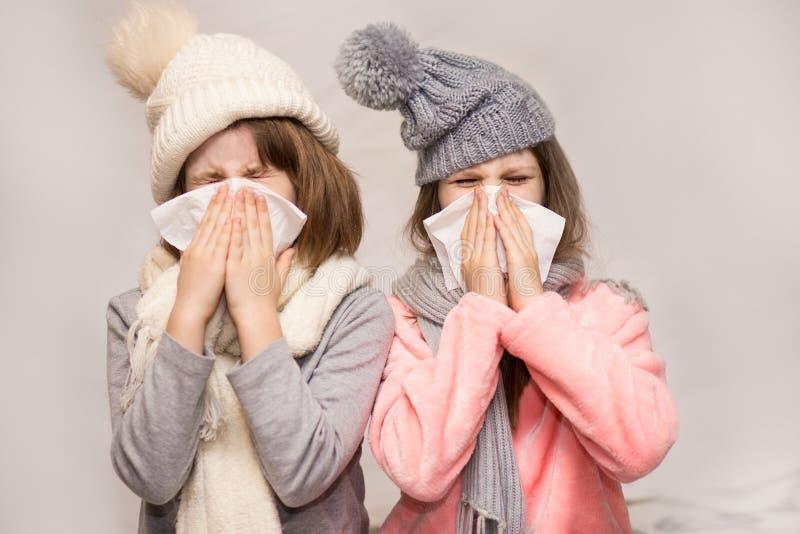 Narizes de sopro doentes das irmãs mais nova com guardanapo junto fotos de stock