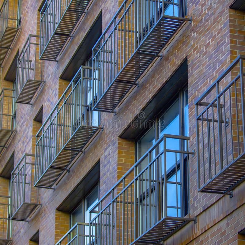 Narrow and airy balconies of a brick building. Close up view of a building`s tiny and open balconies with metal railings and floor. The building has reflective stock photos