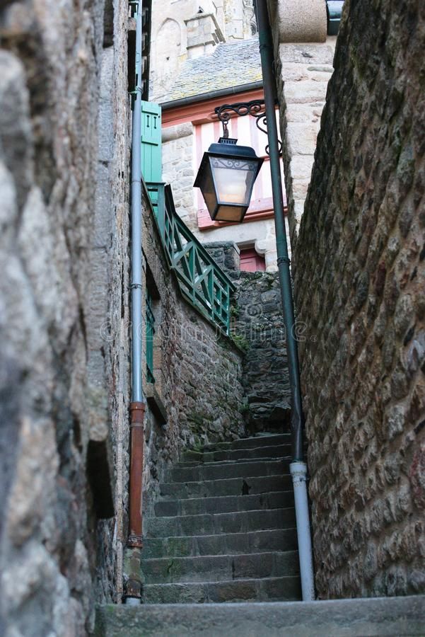 Narrow alley with beautiful steel lantern old fashioned in Mont Saint-Michel monastery architecture european history stock photos