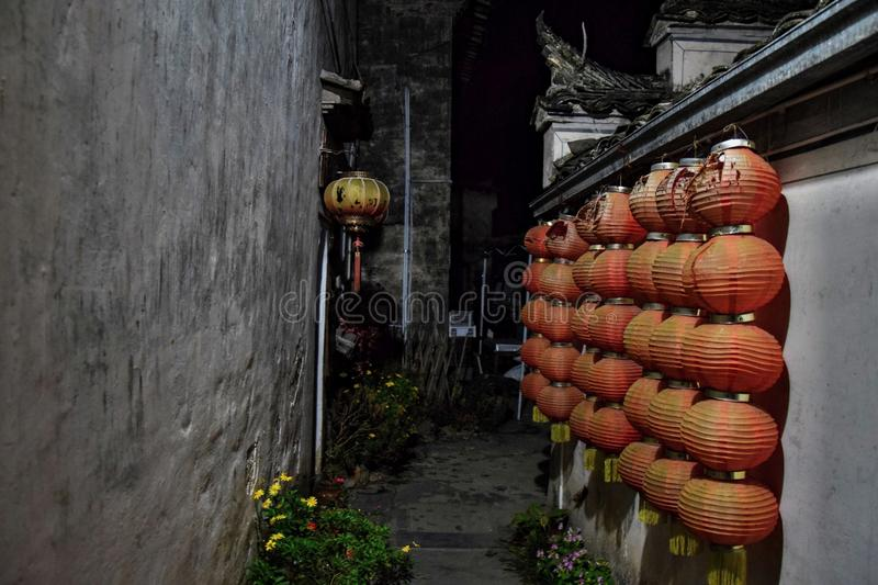 A narrow alley decorated with red lanterns in Xidi, a small ancient village in Anhui province in China. A narrow alley decorated with red lanterns, traditional royalty free stock photography