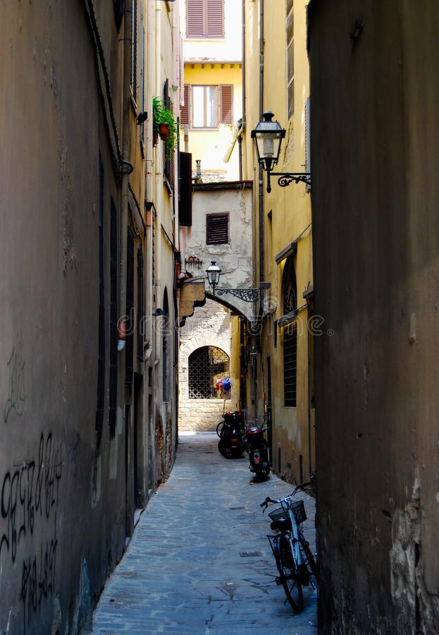 Narrow Alley in Europe. Narrow dark alley with bikes and graffiti royalty free stock images