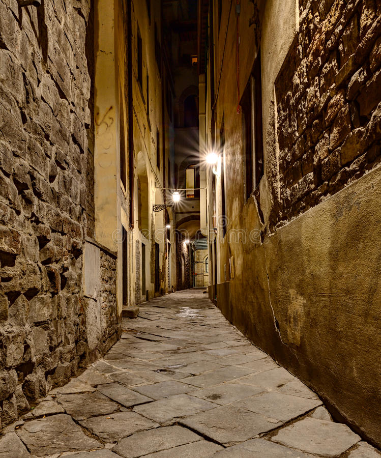 Narrow alley in Florence. Dark narrow alley at night lit by old street lamps in Florence, Tuscany, Italy royalty free stock photos