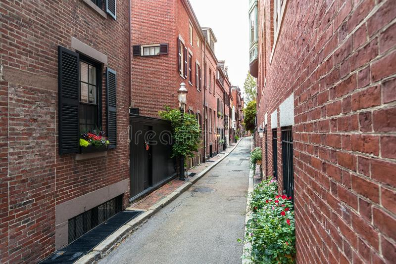 Traditional red brick residential buildings along a deserted narrow alley royalty free stock photography