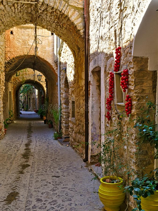 Narrow alley at  medieval castle village. Narrow alley at the medieval castle village of Mesta in Chios island , Greece.  Cherry tomatoes bunches hanging from stock photo
