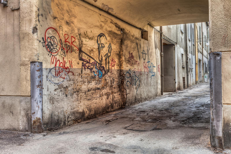 Narrow alley in the old town. Corner of a decadent city street and grunge wall with graffiti stock photos