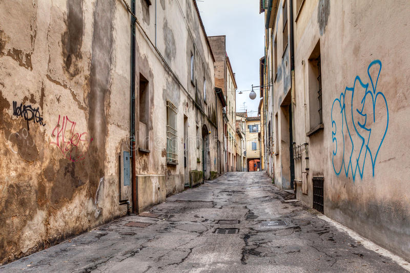 Narrow alley in the old town. Narrow dark alley in the old town - distressed alleyway in the italian city - urban decay, grunge aged street royalty free stock images
