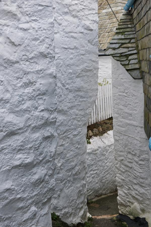 Narrow alley in Port Isaac. Narrow streets wend there way past cottages in Port Isaac. Port Isaac is a traditional fishing village in Cornwall. It is the setting stock images