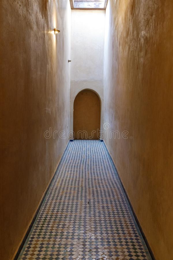 Narrow alley with tiled floor. Narrow interior alley at the Bahia Palace in downtown Marrakech, Morocco royalty free stock image