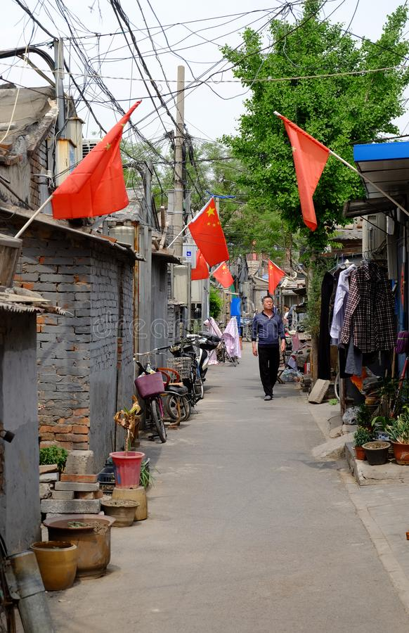 The narrow alley of a traditional hutong in Beijing, China with many Chinese flags during a royalty free stock image