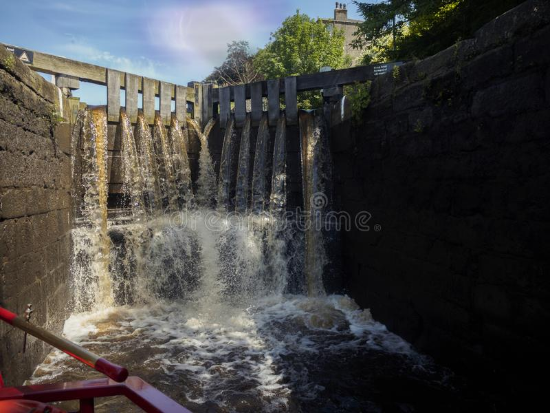 A narrow boat in a canal lock as the lock fills with water. royalty free stock photo