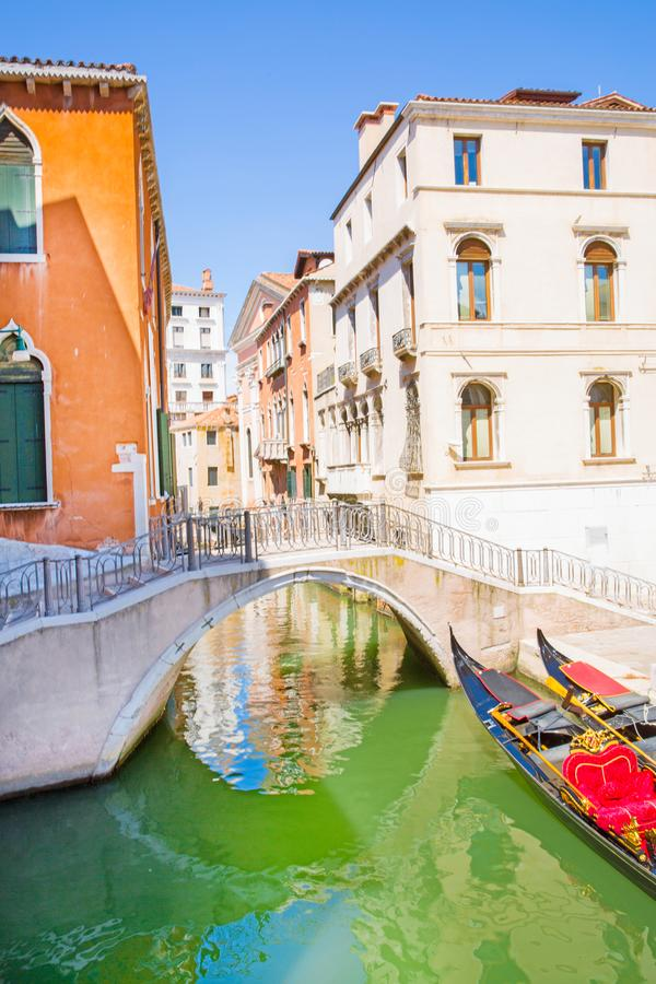Narrow canal and gondola in Venice, Italy. Old colorful buildings and green water. Narrow canal and gondola in Venice, Italy. Old colorful building facades and royalty free stock photography