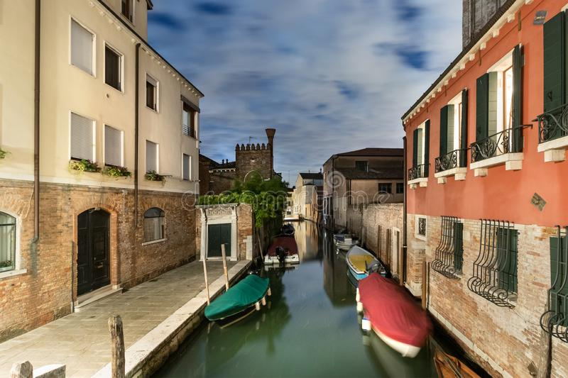 A narrow canal - street with boats in Venice at night, Italy royalty free stock photo