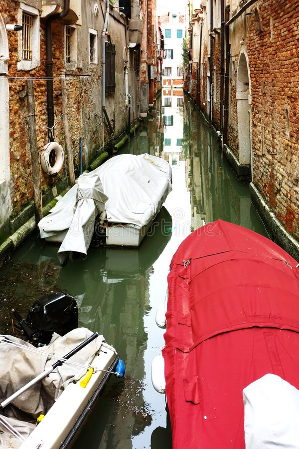Narrow canal in venice with boats stock images