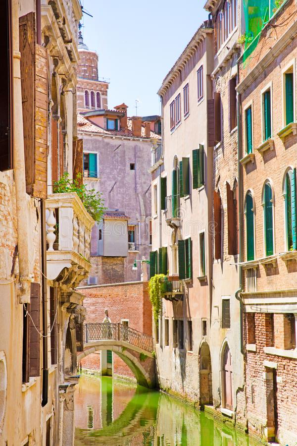 Narrow canal in Venice, Italy. Old buildings reflect in green canal water. Amazing view to the narrow canal in Venice, Italy. Old buildings reflect in green stock images