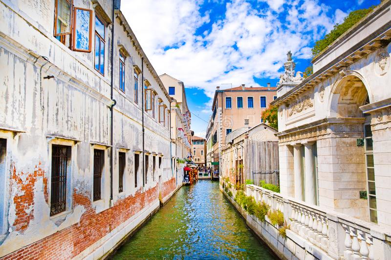 Narrow canal in Venice, Italy. Old historical buildings and bright green water. Bright blue sky stock image