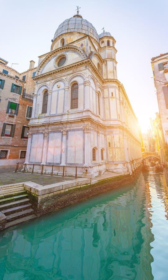 Narrow canal in Venice, near the church near the pier stock photos