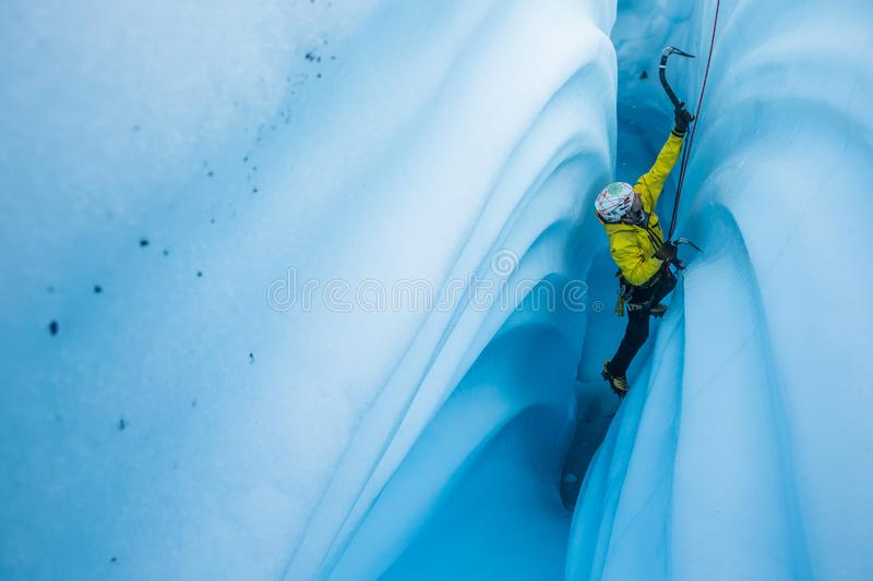 Narrow canyon of ice with wavy walls and an ice climber ascending the narrow slot royalty free stock image