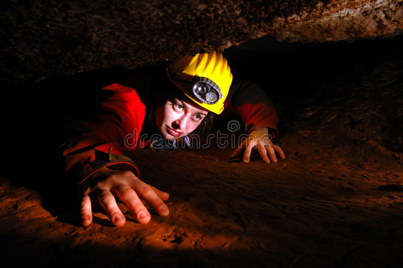Narrow cave passage with a cave explorer royalty free stock photos
