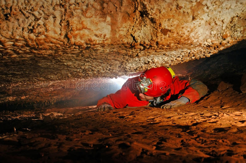 Narrow cave passage with a cave explorer stock image