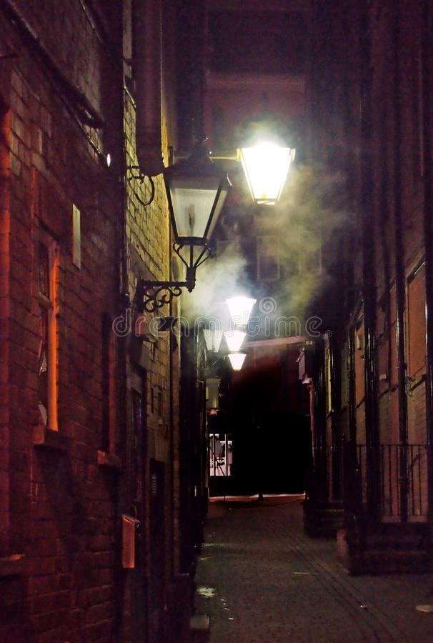 Narrow city alley illuminated by old glowing street lights shining on brick walls with atmospheric swirling fog and dark shadows stock images