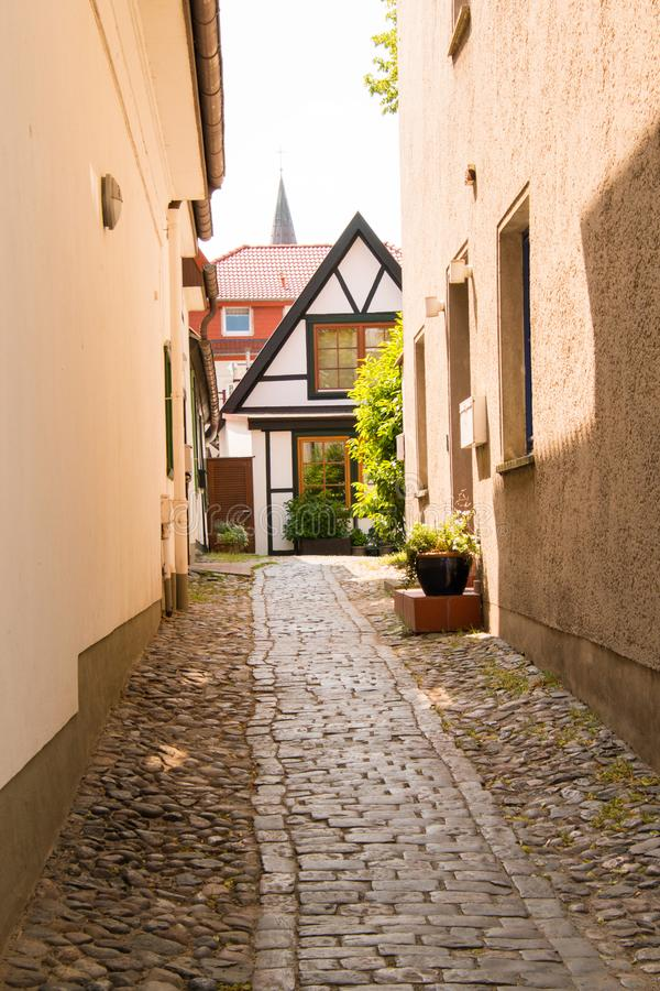 Narrow cobblestone alleyway between buildings with small white house with brown trim at the end. Of the ally royalty free stock photos