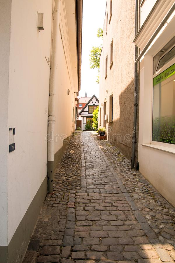 Narrow cobblestone alleyway between buildings with small white house with brown trim at the end. Of the ally stock photography