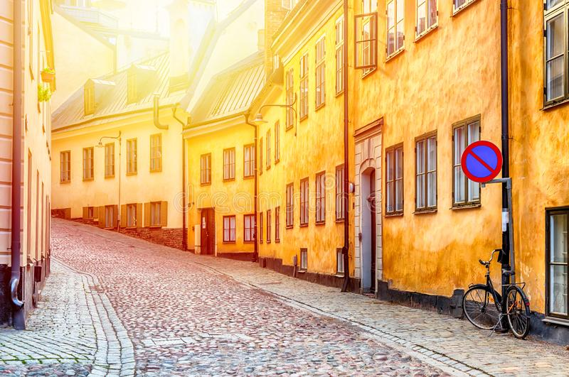 The narrow cobblestone street with a bicycle and yellow medieval houses of Gamla Stan historic old center of Stockholm at summer royalty free stock images