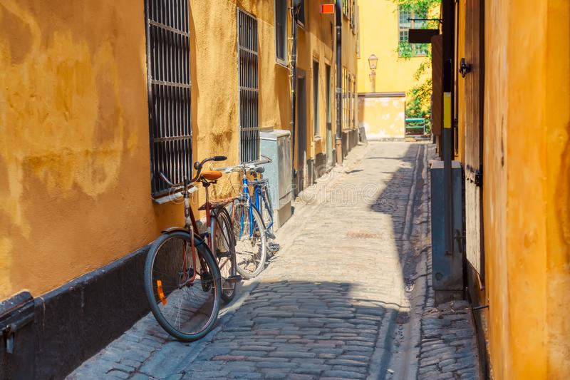 The narrow cobblestone street with a bicycle and yellow medieval houses of Gamla Stan historic old center of Stockholm at summer royalty free stock photo