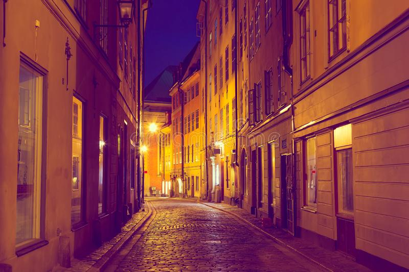 The narrow cobblestone street with medieval houses of Gamla Stan historic old center of Stockholm in the evening twilight sunset. royalty free stock photos