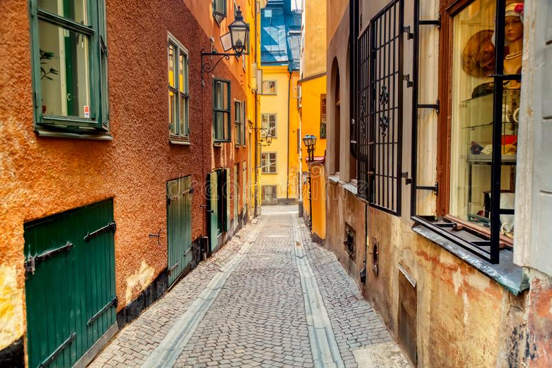 The narrow cobblestone street with medieval houses of Gamla Stan historic old center of Stockholm at summer sunny day stock photography