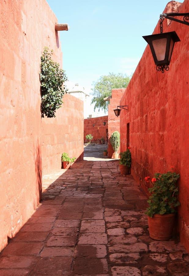Narrow cobblestone street among vibrant orange color old buildings in Monastery of Santa Catalina, Arequipa, Peru royalty free stock photo