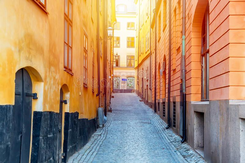 The narrow cobblestone street with yellow medieval houses of Gamla Stan historic old center of Stockholm at summer sunny day royalty free stock images