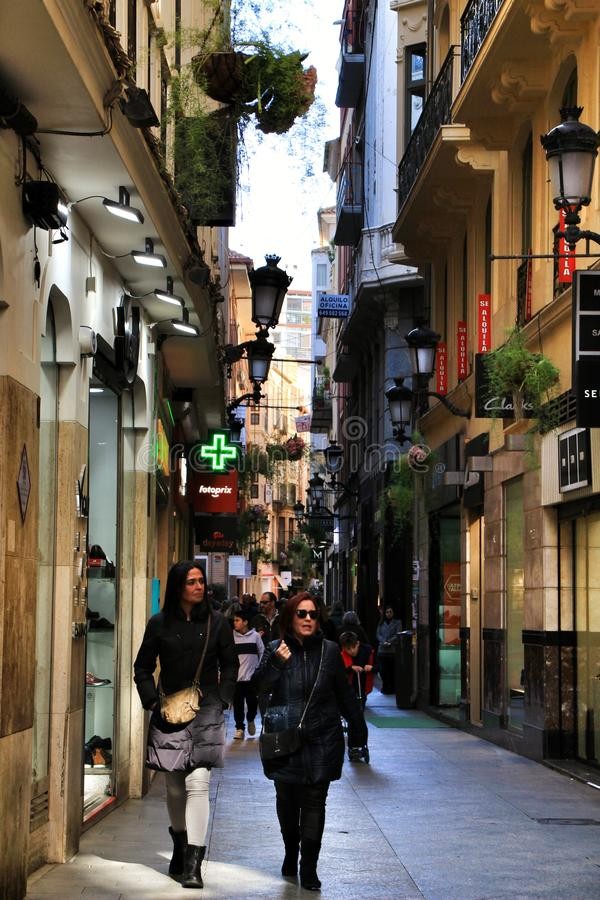 Narrow comercial Plateria street in Murcia. Murcia, Spain- November 16, 2019: Tourist walking through the comercial Plateria street in Murcia narrow building stock photo