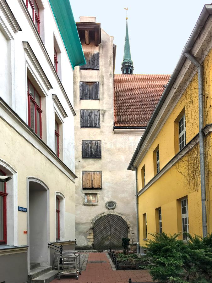Narrow courtyard and barn building in old Riga. Against the background of the spire of St. Peter`s Cathedral stock image