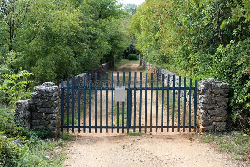Narrow dirt road driveway surrounded with traditional stone wall and dense trees closed with blue fence metal doors with mounted royalty free stock photo