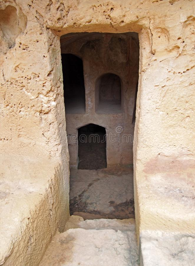 Narrow door carved into rock with steps leading to dark underground chambers at the tombs of the kings in paphos cyprus. A narrow door carved into rock with royalty free stock photo